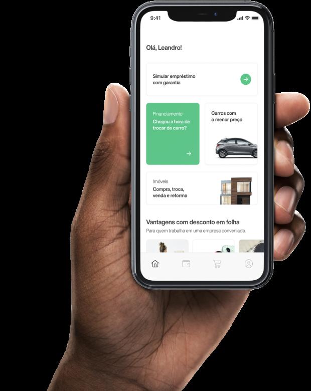 Mão segurando um smartphone, com a tela inicial do App da Creditas